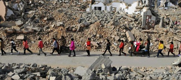 Primary school students walk through the ruins of a demolition area surrounding their school, after class in Zhengzhou, Henan province, China, January 9, 2015. REUTERS/Stringer